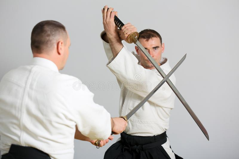 Sword fight. Fighter reflects the attack of the enemy with a samurai sword stock photo