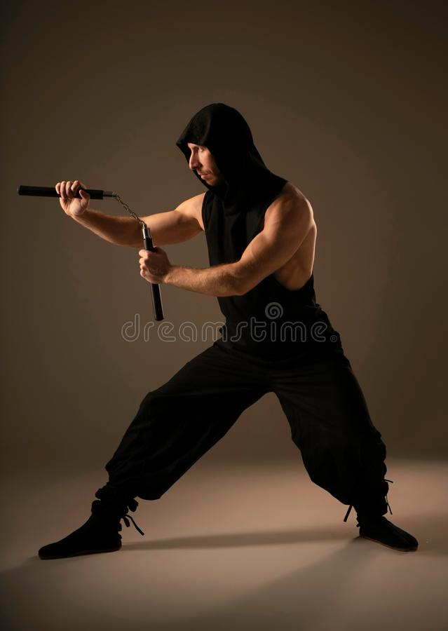 Fighter showing his Wushu skill with nunchuck stock photo