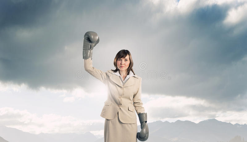 She is fighter. Young businesswoman in green boxing gloves competition ready royalty free stock photo
