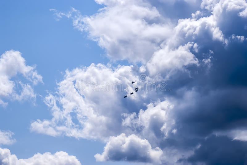 Fighters in the air... Photo of five army fighters (Russian military air force units) flying in the air making aerobatics elements; heavy dark blue clouds in royalty free stock images