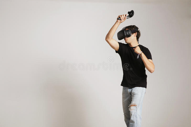 Fighting in VR glasses. Young man in blank black t-shirt gaming golf or tennis in VR headset hitting someting on white royalty free stock photos