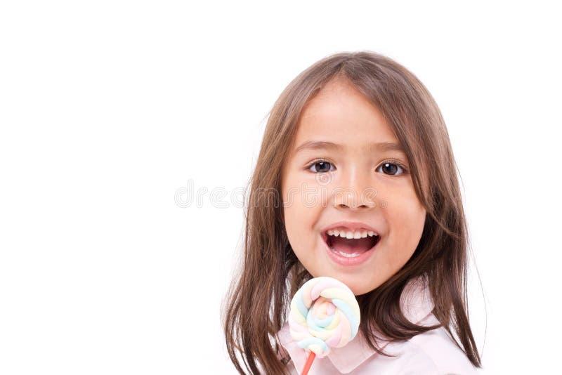 Figlarnie śliczna mała dziewczynka z słodkim kolorowym marshmallow zdjęcie stock