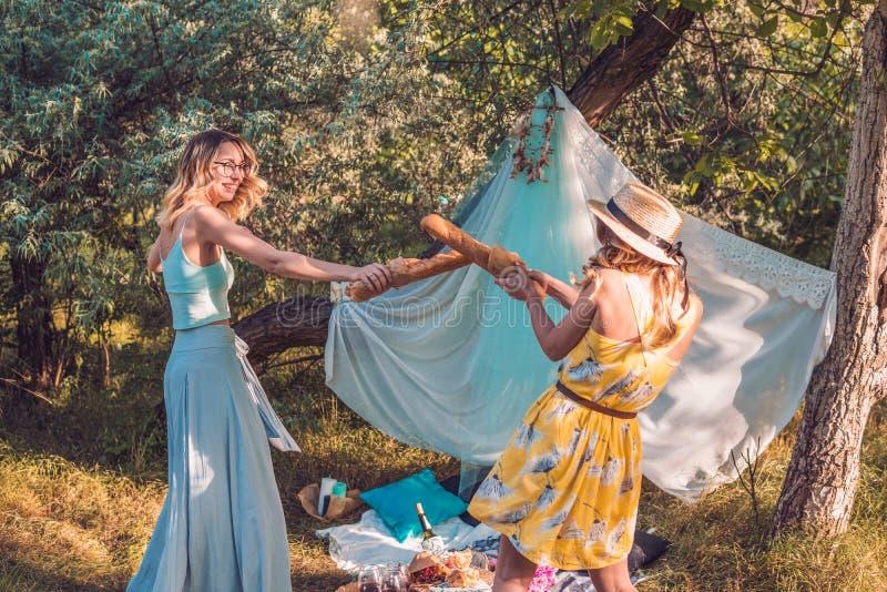Figlarnie dziewczyny walczy z chlebowym baguette robi pinkinowi obraz royalty free
