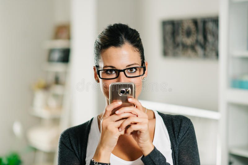 Figlarnie kobieta używa smartphone w domu obraz royalty free