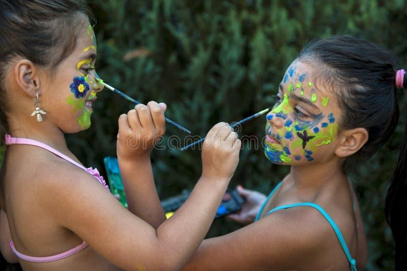 Figlarnie młode dziewczyny malująca dziecko twarz zdjęcia stock