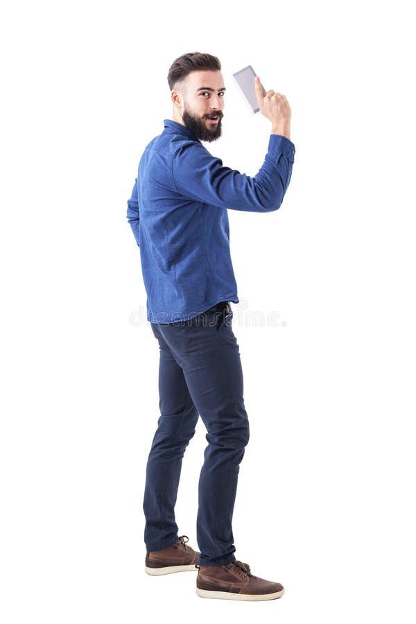 Figlarnie młody dorosły biznesowego mężczyzna mienia telefon komórkowy jako pistolecik i patrzeć kamerę zdjęcie royalty free