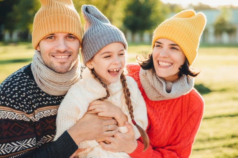 Figlarnie małe dziecko z pigtails jest ubranym ciepłych ubrania, wydaje czas wolnego z uroczymi czule rodzicami, szczęśliwego wyr obrazy stock