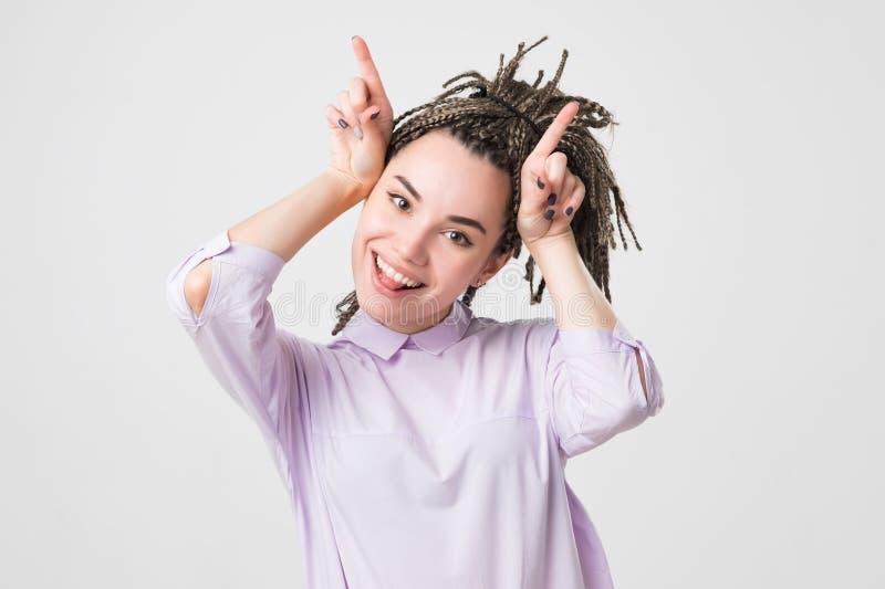 Figlarnie nastoletnia dziewczyna z warkoczy przedstawień rogami fotografia royalty free