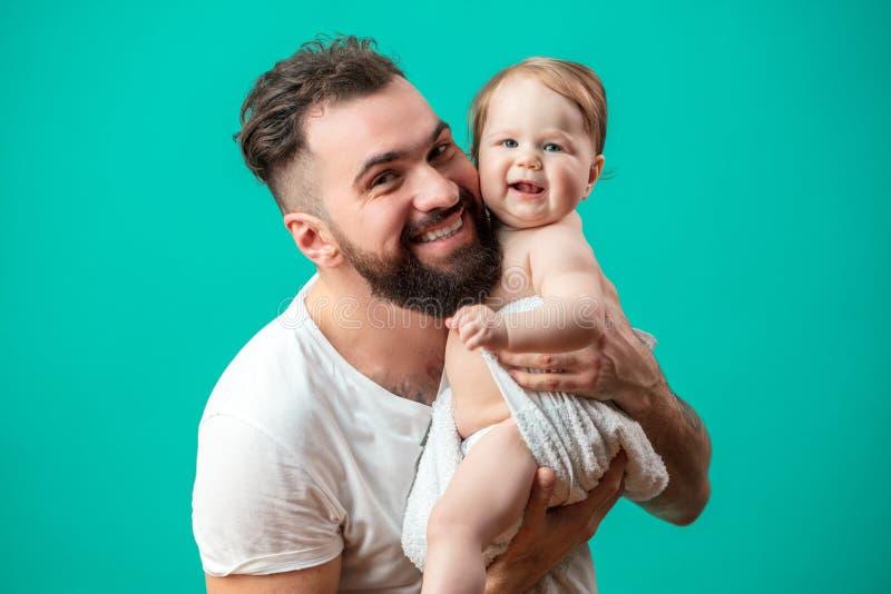 Figlarnie ojciec niesie jego uśmiechniętego dziecięcego dziecka na szyi nad błękitnym tłem obraz royalty free