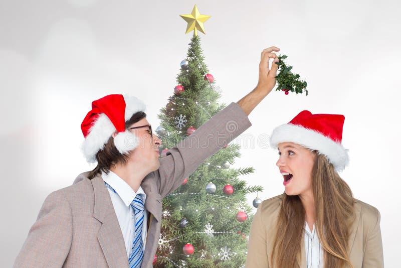 Figlarnie para w Santa kapeluszowej trwanie pobliskiej choince fotografia royalty free