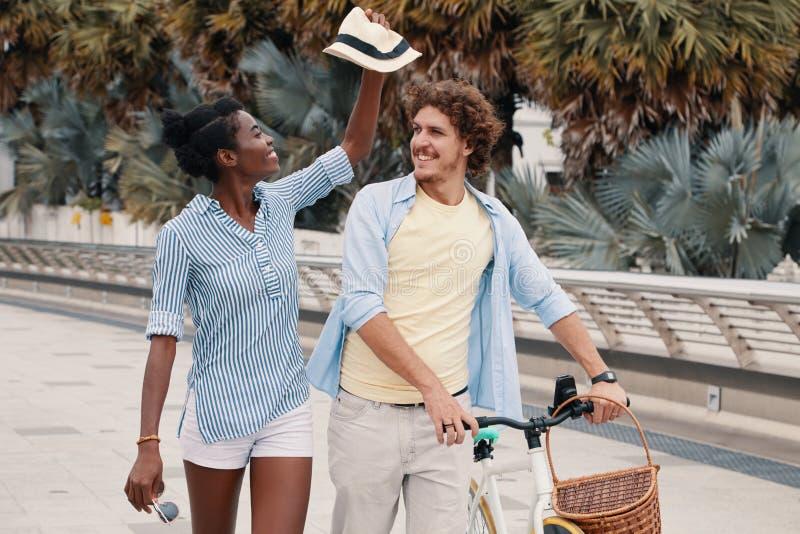 Figlarnie para z rowerowym odprowadzeniem na ulicie obrazy stock