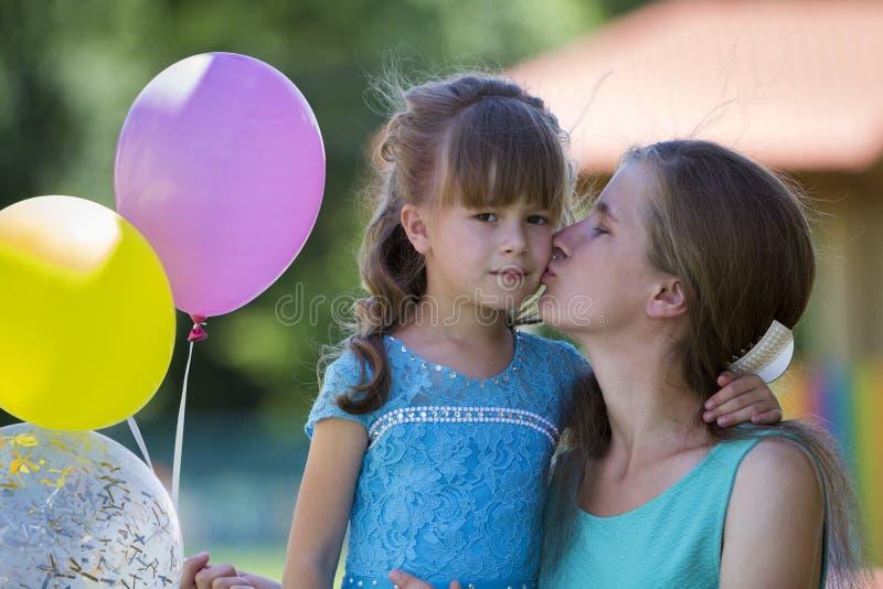 Figlarnie piękna blond mała dziewczyna z kolorowymi balonami w nic zdjęcia royalty free