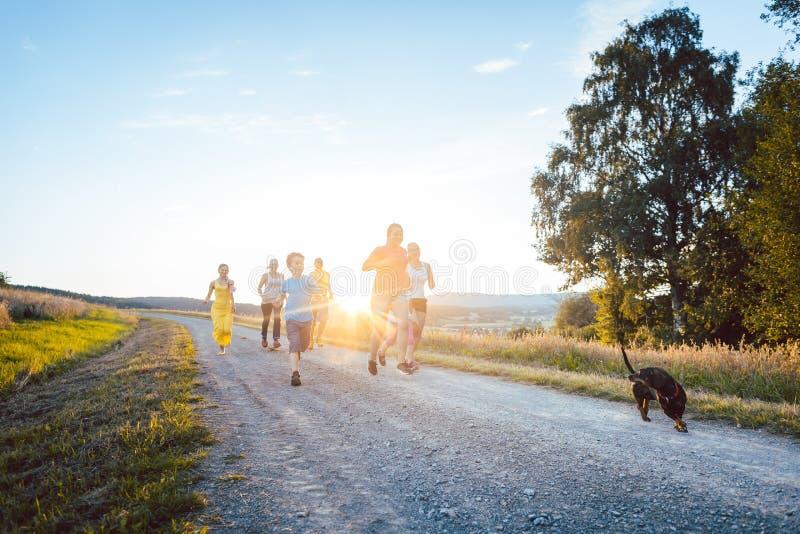 Figlarnie rodzinny bieg i bawić się na ścieżce w lato krajobrazie zdjęcie stock