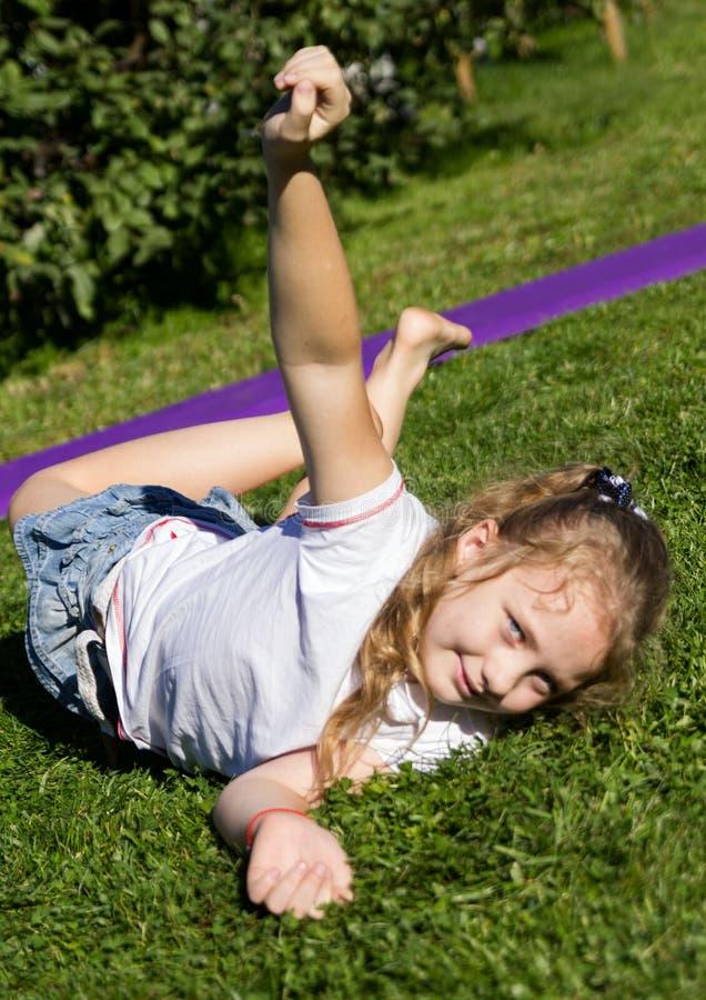 Figlarnie szczęśliwa mała dziewczynka odpoczywa na trawie w lato parku zdjęcia stock