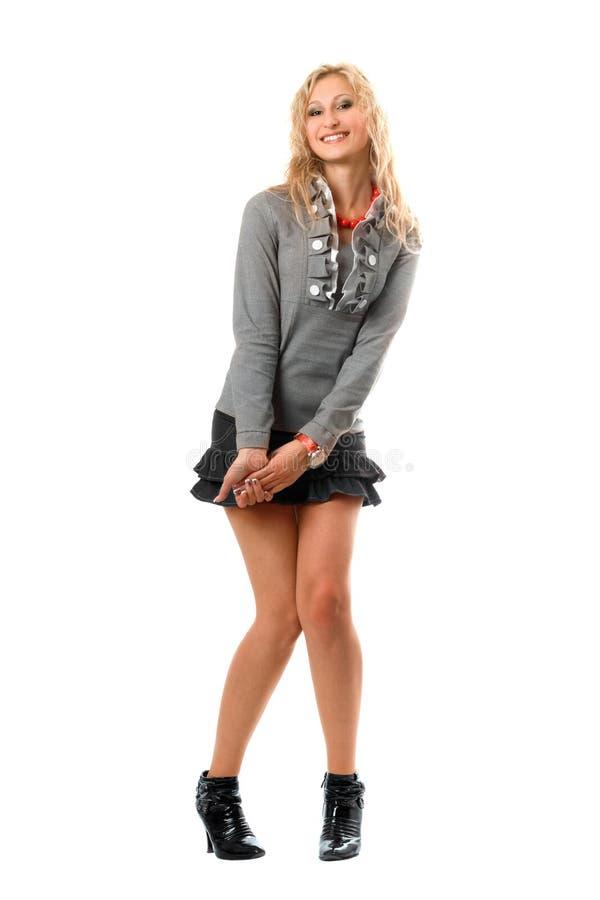 Figlarnie uśmiechnięta blondynka w szarej spódnicie obraz stock