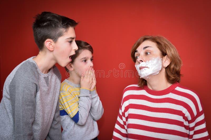 Figli e madre con la rasatura della schiuma sul suo fronte immagini stock libere da diritti