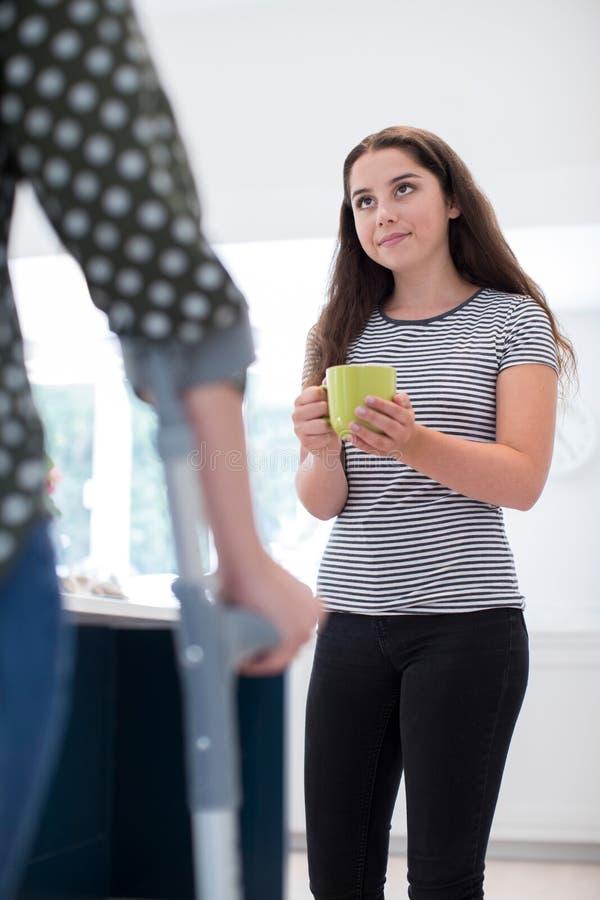 Figlia adolescente che fa bevanda per il genitore disabile fotografia stock libera da diritti