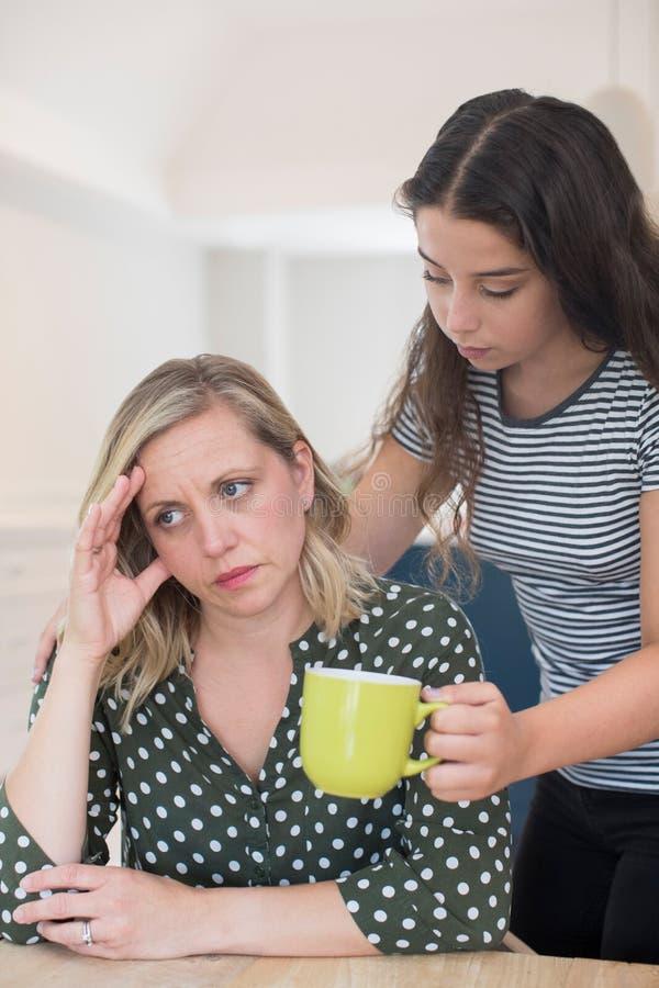 Figlia adolescente che fa bevanda per il genitore che soffre con la H mentale immagini stock libere da diritti