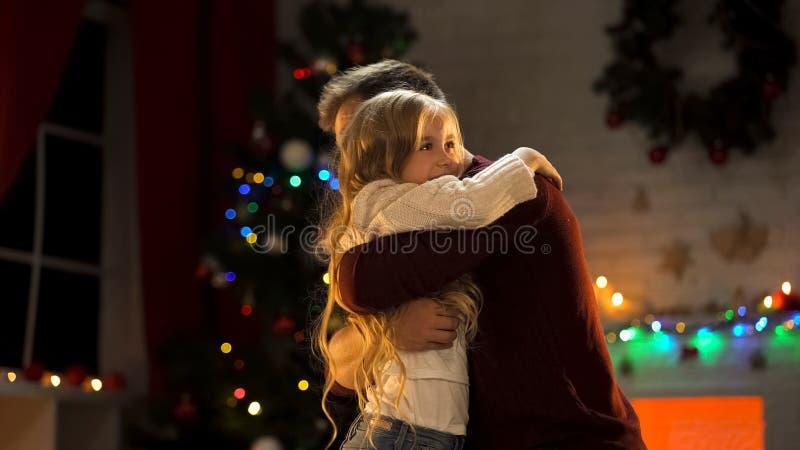 Figlia adorabile d'abbraccio del padre vicino all'albero di Natale, feste felici insieme fotografia stock