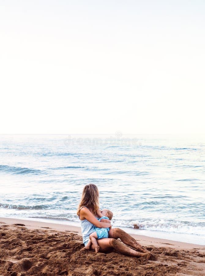 Figlia breasfeeding del bambino della giovane madre sulla spiaggia sulla vacanza estiva immagini stock libere da diritti