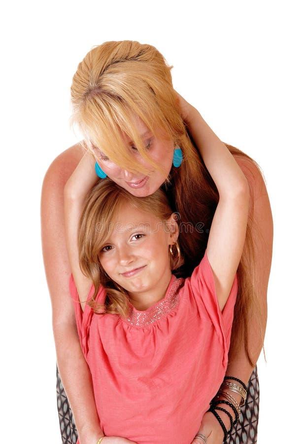 Figlia che abbraccia mamma fotografia stock