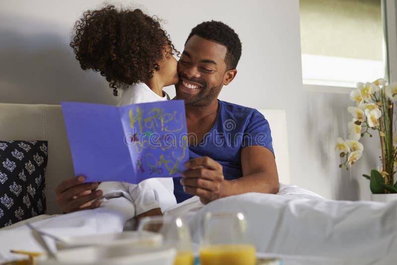 Figlia che bacia il suo papà a letto sulla sua mattina di compleanno immagini stock libere da diritti