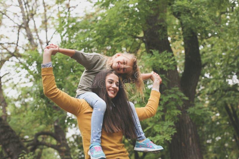 Figlia che gioca con la mamma Madre che porta sua figlia sullo shou immagini stock libere da diritti