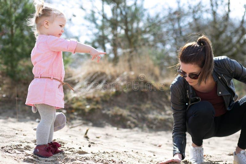 Figlia che indica e che si diverte con la madre fotografia stock