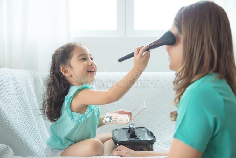Figlia che mette trucco sul suo fronte della madre a casa fotografie stock