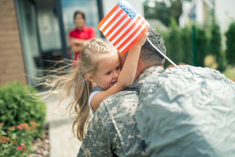 Figlia che tiene poca bandiera americana che abbraccia strettamente papà fotografia stock