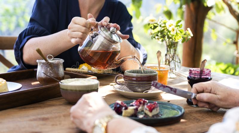 Figlia che versa tè caldo per la madre fotografie stock libere da diritti