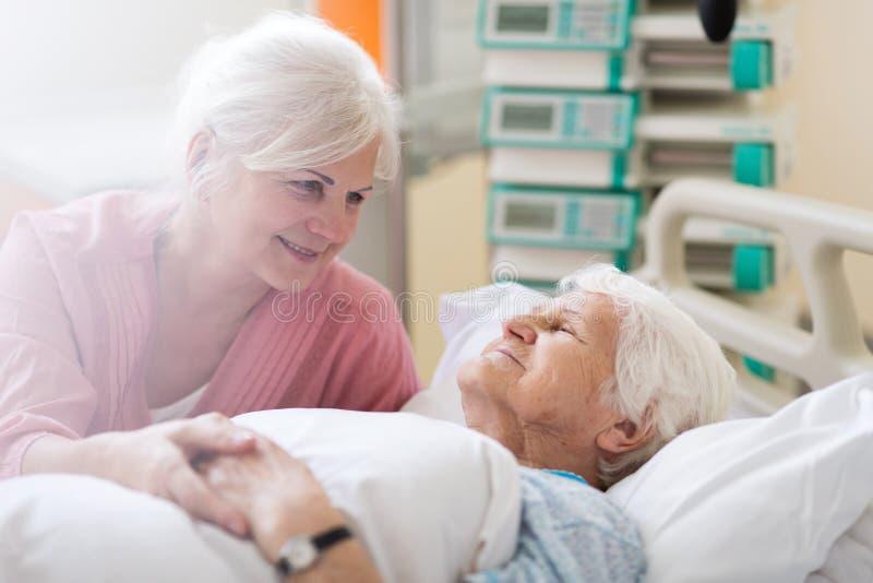Figlia che visita sua madre senior in ospedale immagine stock libera da diritti
