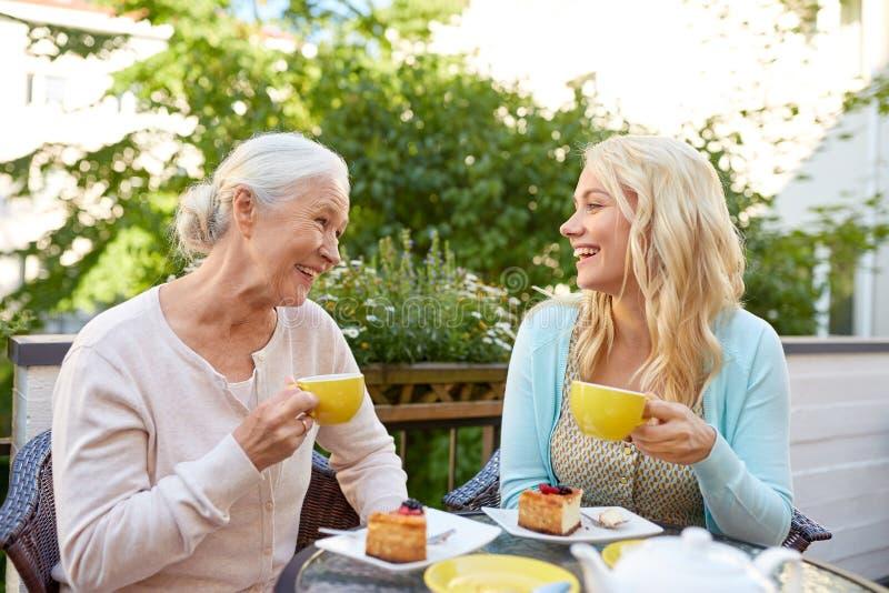 Figlia con il tè bevente della madre senior al caffè fotografie stock