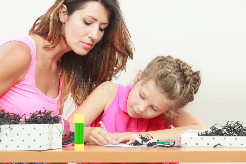 Figlia d'aiuto della mamma con lavoro immagine stock