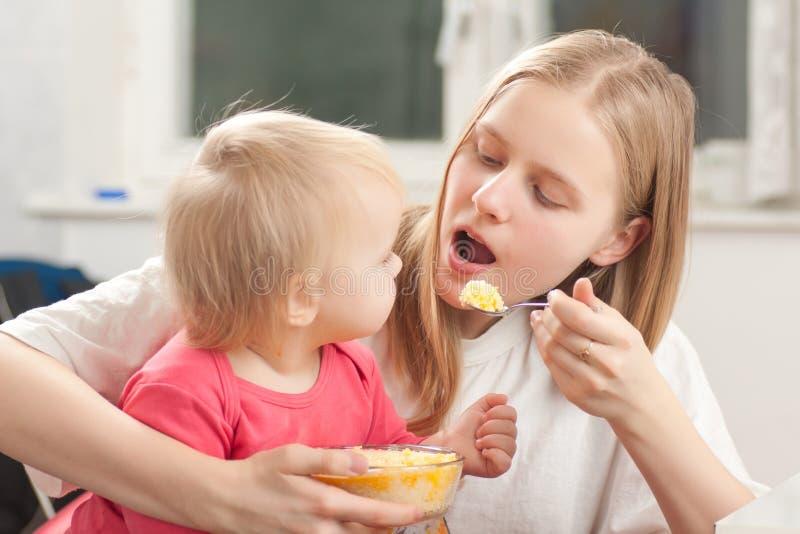 Figlia d'alimentazione della madre con porridge fotografia stock
