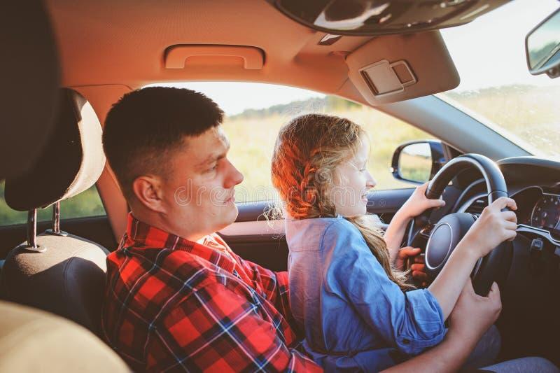 Figlia d'istruzione del bambino del padre per condurre un'automobile, viaggio della famiglia immagini stock