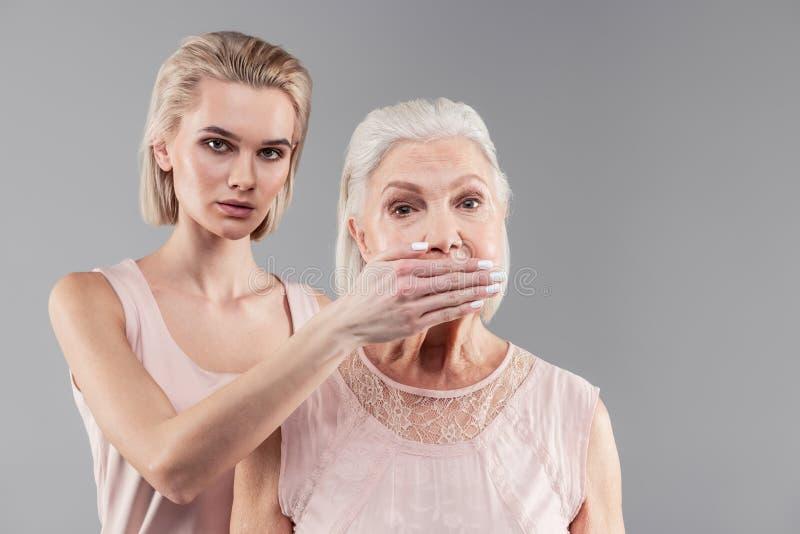 Figlia dai capelli corti diabolica categoricomente che chiude bocca della donna spaventata fotografie stock