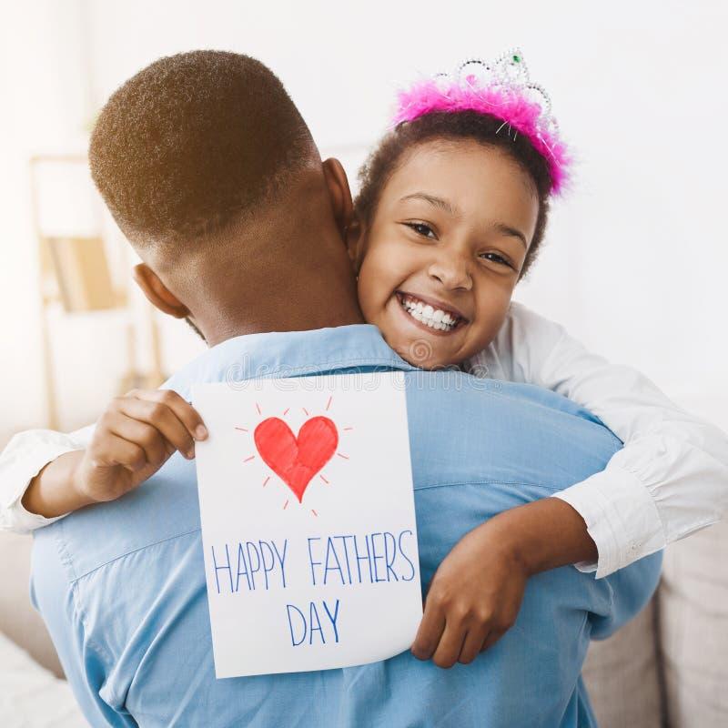 Figlia del bambino che abbraccia papà e le che dà cartolina immagini stock