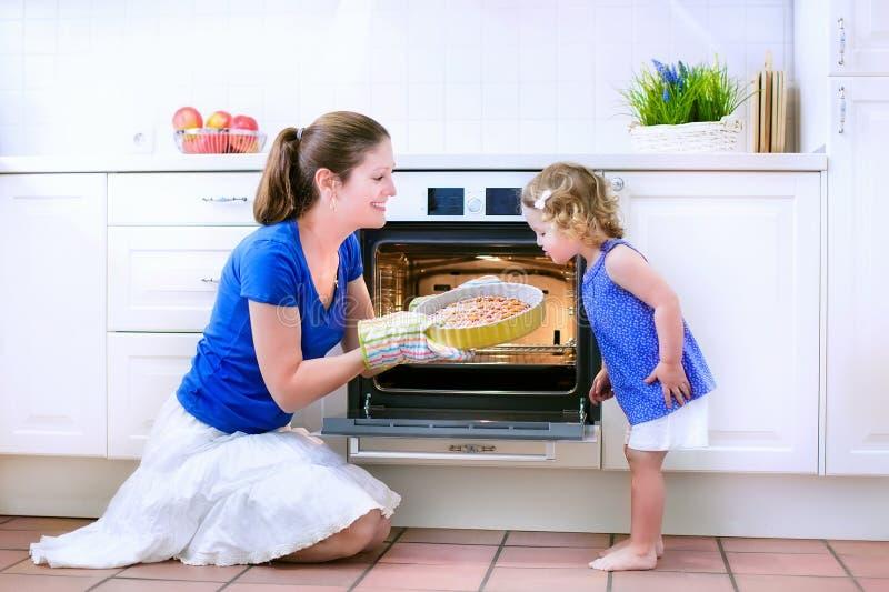 Figlia del bambino e della madre che cuoce una torta fotografie stock libere da diritti