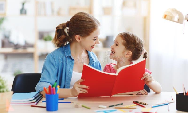 Figlia del bambino e della madre che fa scrittura e la lettura di compito a casa fotografia stock