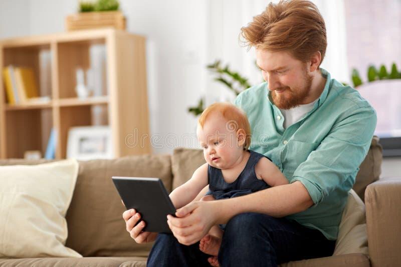 Figlia del bambino e del padre con il pc della compressa a casa fotografie stock libere da diritti