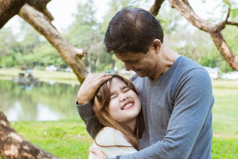 Figlia dell'abbraccio del padre una piccola nel parco immagini stock libere da diritti