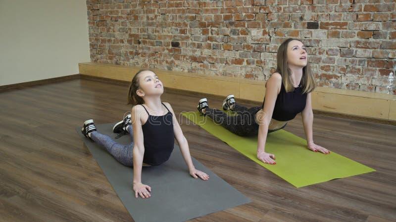 Figlia della mamma di asana di yoga della famiglia di forma fisica di sport immagini stock