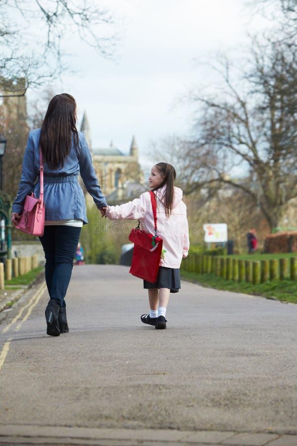 Figlia di camminata della madre alla scuola lungo il percorso immagini stock libere da diritti