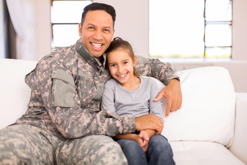 Figlia di seduta del padre militare immagini stock