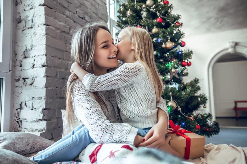 Figlia felice che bacia sua madre sopra il fondo delle luci dell'albero di Natale immagini stock libere da diritti