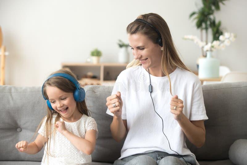 Figlia felice del bambino e della madre che ascolta la musica in cuffie immagini stock