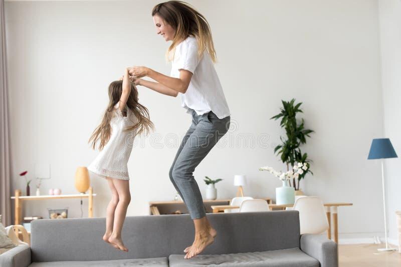Figlia felice del bambino e della mamma che si tiene per mano salto sul sofà immagine stock