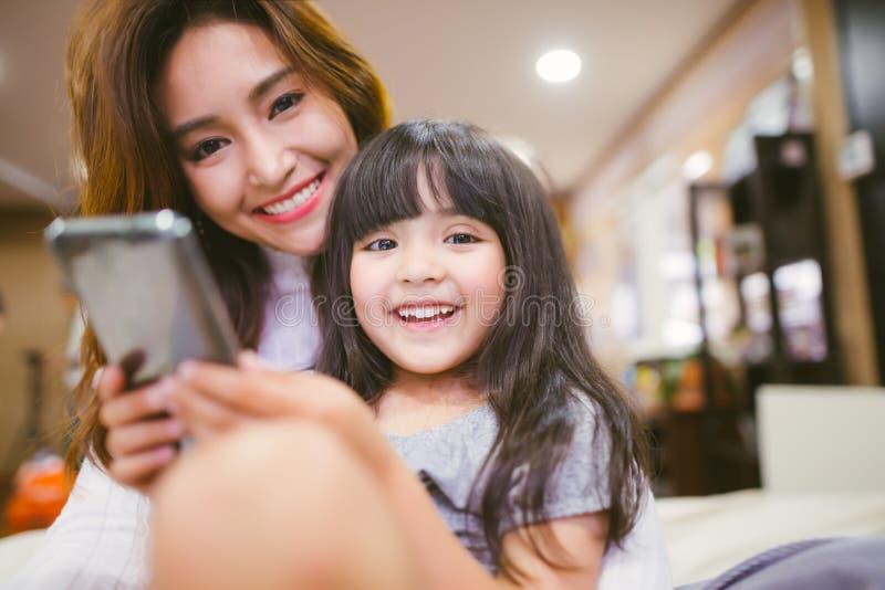 Figlia felice del ritratto che gioca smartphone con sua madre immagine stock