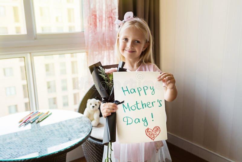 Figlia piccola che tiene cartolina e mazzo dipinti dei fiori per la mamma Concetto felice di giorno di madre immagine stock libera da diritti